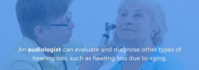 audiologist looking at patient's ears with otoscope