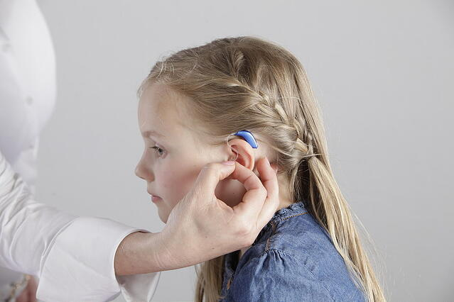 girl receiving a hearing aid fitting