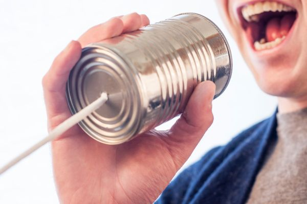 man shouting into a tin can telephone